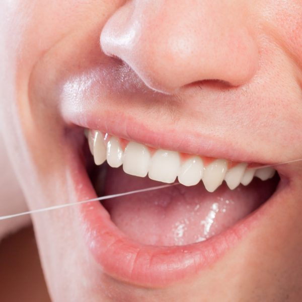 Daily health care. Young man cleaning flossing his white teeth with dental floss